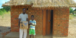 two Malawai boys standing in front of a hut holding a Manna Pack