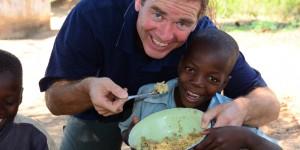 David Morrison assisting boy with food