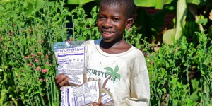 """a boy holding """" Impact Lives"""" Bags full of food"""