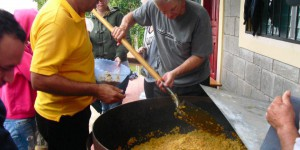 giant pot full of beans and rice being served to people